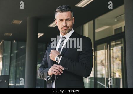 Porträt eines erfolgreichen jungen Geschäftsmann im Anzug vor einem Glas Gebäude gekleidet und berühren seine Hülse - Stockfoto