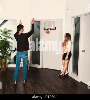 Zwei junge tausendjährigen Business Mitarbeiter eine Pause am Arbeitsplatz und schießen einen Basketball in einen Net; Sherwood Park, Alberta, Kanada - Stockfoto