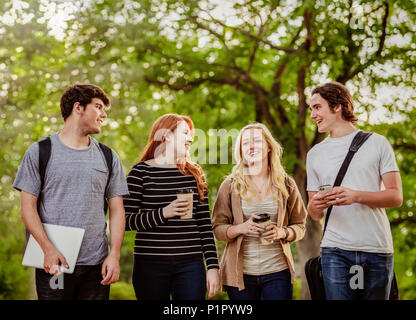 Vier Freunde Wandern und gemeinsam im Gespräch auf dem Campus der Universität; Edmonton, Alberta, Kanada - Stockfoto