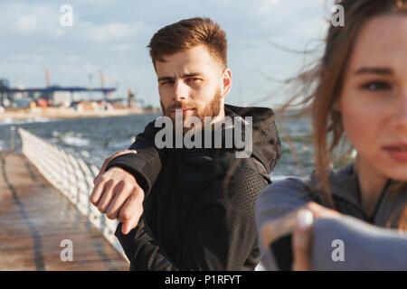 Junge sport Paar tun Dehnübungen vor dem Joggen am Strand konzentriert - Stockfoto