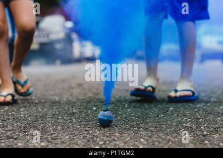 Blauer Rauch Bombe auf der Straße rauchen mit Kindern im Hintergrund - Stockfoto