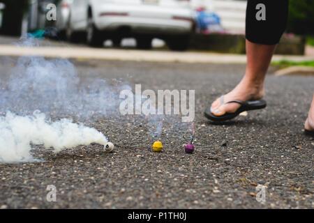 Drei Rauchbomben durch Frau Fuß in der Straße - Stockfoto