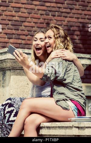 Zwei weibliche Studenten sitzen zusammen auf dem Campus, albern und ein Selbstporträt mit Ihrem Smart Phone - Stockfoto