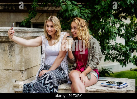 Zwei weibliche Studenten sitzen zusammen auf dem Campus ein Selbstporträt mit Ihrem Smart Phone; Edmonton, Alberta, Kanada - Stockfoto
