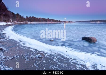 Aufgehenden Mond an einem kalten Winterabend am Oslofjord, im Ofen in Råde, Østfold Norwegen. - Stockfoto