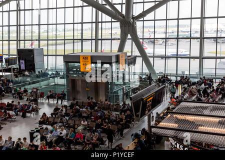 LONDON - 27. MAI 2018: Massen von Menschen in der Abfahrt an Bord Flugzeug am Flughafen London Heathrow warten - Stockfoto