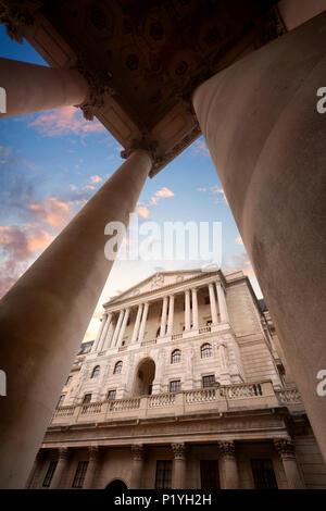 Die Bank von England Hauptsitzt auf Threadneedle Street in der City von London, England, gesehen durch die Spalten der Royal Exchange bei Sonnenuntergang - Stockfoto