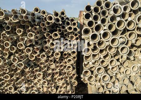 Bewässerung metallischen Rohrleitungen im Freien aus Gießen Saison gestapelt. Letzten Sonnenuntergang Strahlen - Stockfoto