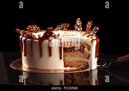 Runde weiße Kuchen mit Karamell und Schokolade Puffreis auf ein rundes Tablett auf schwarzem Hintergrund - Stockfoto