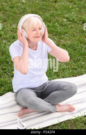 Ältere Frau Musik hören mit Kopfhörern beim Sitzen auf Yoga Matte - Stockfoto