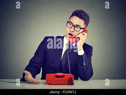 Angewidert junger Mann empfängt fehlerhafte Nachrichten schockiert über das Telefon - Stockfoto