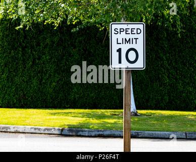 Zehn Meilen pro Stunde Höchstgeschwindigkeit Zeichen mit grünen Büschen und Bäumen - Stockfoto