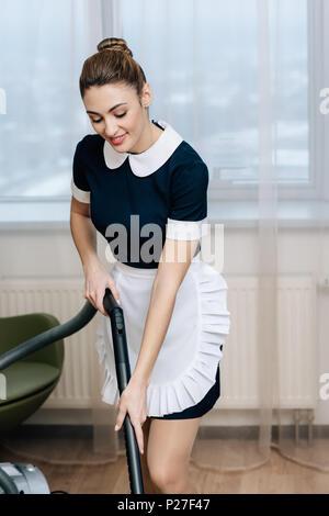 Junge lächelnde Mädchen in Uniform mit Staubsauger - Stockfoto