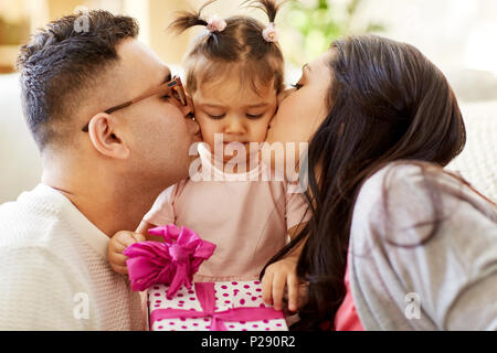 Eltern küssen kleine Tochter mit Geburtstagsgeschenk - Stockfoto