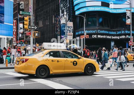 Gelbes Taxi wartet an der Ampel in New York, Fußgänger vor. - Stockfoto