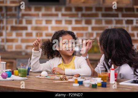 Afrikanische amerikanische Mutter Malerei Tochter Gesicht, Ostern Konzept - Stockfoto