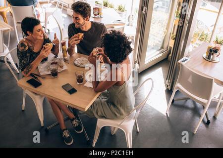 Hohe Betrachtungswinkel von drei junge Freunde Burger in ein Restaurant. Kleine Gruppe von Mann und Frauen sitzen um cafe Tabelle reden und Essen. - Stockfoto
