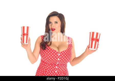 Aufgeregt Plus size Frau im roten Kleid mit Popcorn Boxen isoliert auf weißem - Stockfoto