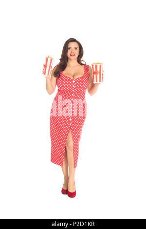 Lächelnd Plus size Frau im roten Kleid mit Boxen von Popcorn isoliert auf weißem - Stockfoto