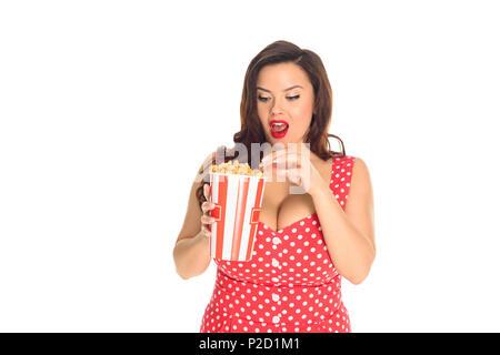 Schockiert Plus size Frau im roten Kleid essen Popcorn isoliert auf weißem - Stockfoto