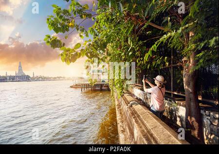 Frau Tourist, der ein Bild von Wat Arun mit Ihrem Telefon bei Sonnenuntergang in Bangkok, Thailand - Stockfoto