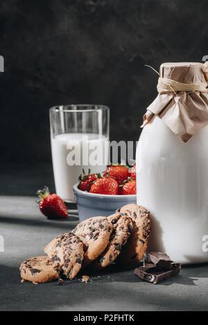 Nahaufnahme der Chocolate Chip Cookies mit Milch und Erdbeeren Stockfoto