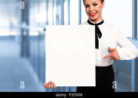 Schöne Geschäftsfrau und lächelnd ein weißes Schild mit Kopie Platz für Werbung und Text auf einem unscharfen Hintergrund des Amtes. - Stockfoto