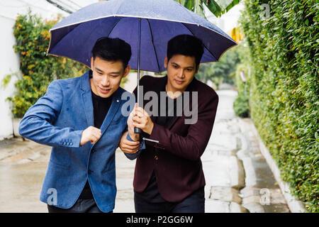 Ein schwules Paar mit Sonnenschirm und Hände zusammen. Asiatische homosexuelle Männer wandern im Regen - Stockfoto
