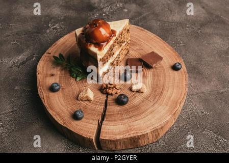 Leckeres Stück Kuchen mit Schokolade und Heidelbeeren auf Holzbrett - Stockfoto