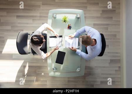 Ansicht von zwei Geschäftsleute halten Resume über Schreibtisch im Büro - Stockfoto