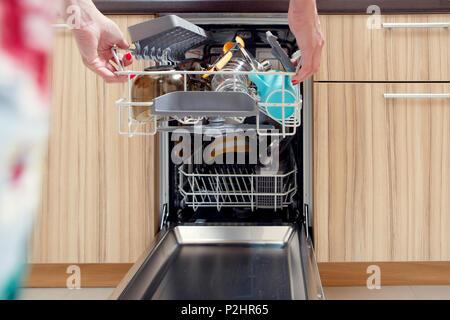 Bild von der Hand des Mädchens Eröffnung Spülmaschine mit schmutzigen Geschirr - Stockfoto