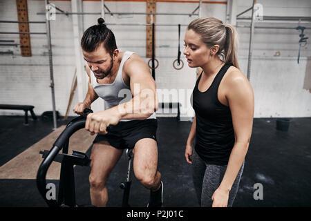 Passen junge Mann in Sportkleidung, einem stationären Fahrrad während ein Fitnessstudio Workout mit einem Freund beobachten - Stockfoto