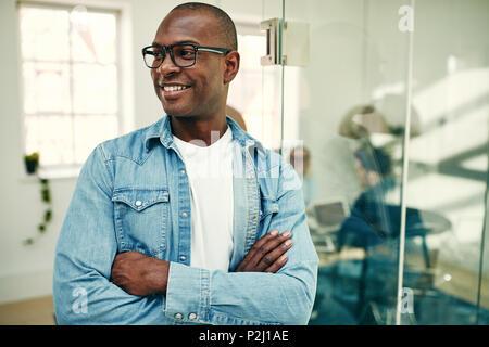 Lächelnden jungen afrikanischen Geschäftsmann lehnte sich mit seinen Waffen gegen eine Glaswand in einem Büro mit Kollegen im Hintergrund gekreuzt - Stockfoto