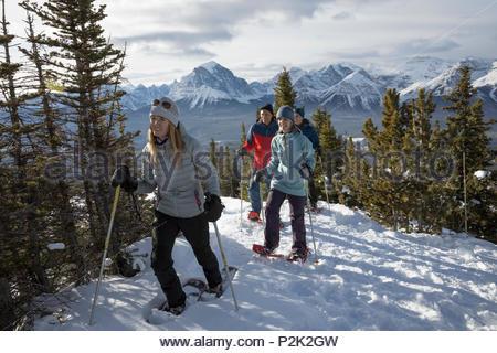 Active Senior paar Freunde Schneeschuhwandern auf Sunny Mountain - Stockfoto