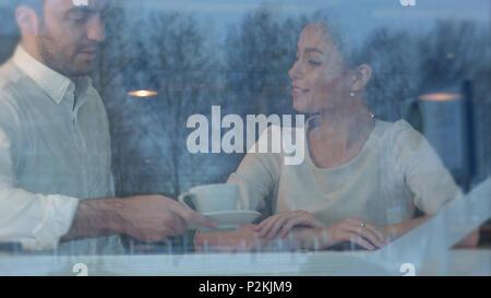 Lächelnd Kellner briniging Kaffee zu weiblichen Client im Cafe - Stockfoto