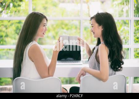 Zwei junge asiatische schöne fröhliche Frau im Sitzen auf Kaffee Cafe lachen und trinken Kaffee aus einem weißen Tassen. - Stockfoto