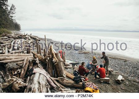 Freunde genießen Wochenende surfen Kurzurlaub, Entspannung am Lagerfeuer auf robusten Strand - Stockfoto