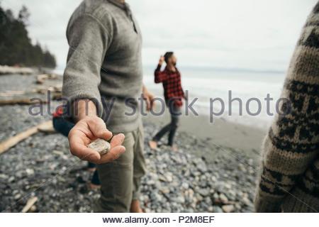 Mann werfen Steine mit Freunden auf robusten Strand - Stockfoto
