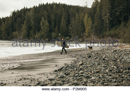Männliche Surfer mit Hund mit Surfbrett auf robusten Strand - Stockfoto