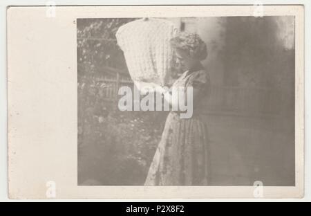 Die tschechoslowakische SOZIALISTISCHE REPUBLIK - AUGUST 1958: Vintage Foto zeigt eine junge Frau hängt ein wolliges Weste auf einer Wäscheleine. Retro Schwarz/Weiß-Fotografie. - Stockfoto
