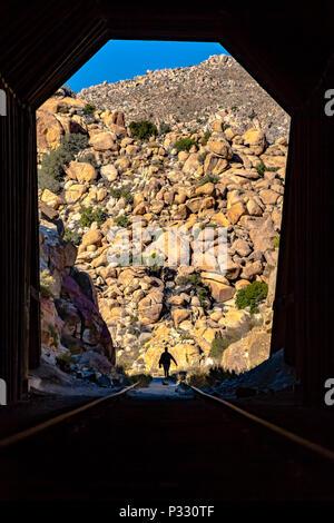 Mann mit der Kamera in der Silhouette auf Schienen. Innerhalb eines Tunnels mit Rocky Mountain als Hintergrund. - Stockfoto