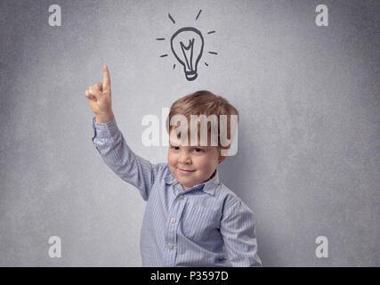 Smart little Junior vor einer grauen Wand aufgestellt mit kindlicher Konzept - Stockfoto