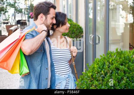 Junge glückliches Paar mit Tüten in der Stadt während der saisonalen Verkäufe - Stockfoto