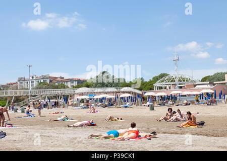 Menschen beim Sonnenbaden auf Blue Moon Beach, Lido di Venezia, die Insel Lido, Venedig, Venetien, Italien, auf einer sonnigen späten Frühling. Pier, Restaurants, Beobachtung - Stockfoto