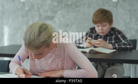 Ein junges Mädchen in einem Klassenzimmer Konzentration auf Ihr Test, während ihre Mitschüler Spielen auf dem Smartphone