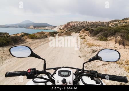 ATV Quad Bike auf der Küstenstraße entlang Ägäis auf Milos, Griechenland geparkt. Blick vom Fahrersitz - Stockfoto