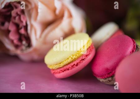 Kuchen Makronen auf rosa Hintergrund. Close up Macaron Dessert auf der Ansicht von oben. Bunte almond Cookies in Pastell rosa, gelben Farben. Vintage toning Stil. - Stockfoto