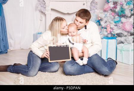 Portrait von Happy Family vor Weihnachtsbaum - Stockfoto