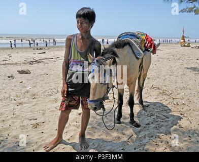 Die jungen Burmesischen boy steht mit weißen Pony auf setse Beach in der Nähe von Mawlamyine, South Myanmar bietet Fahrten mit einheimischen Paddeln im Meer im Hintergrund - Stockfoto