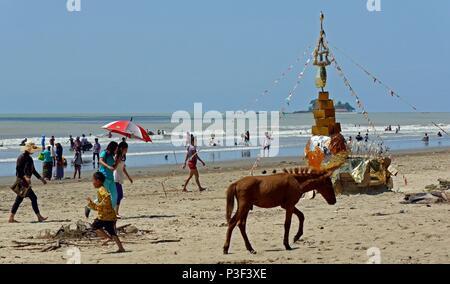 Setse Beach in der Nähe von Mawlamyine, South Myanmar mit buddhistischen Heiligtum auf Sand inmitten Kinder schwimmen, Menschen zu Fuß und ein braunes Pony traben durch - Stockfoto